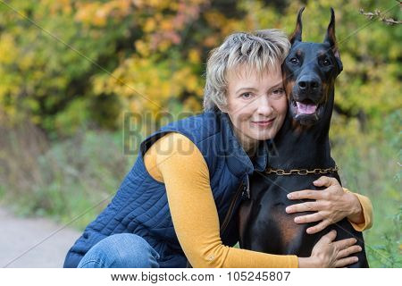 Smiling woman is hugging the dobermann in a park.