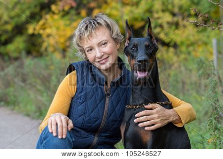Happy woman is sitting on walkway and hugging the dobermann in a park.
