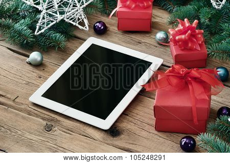 White Tablet Computer With Christmas Present On Wooden Table Closeup