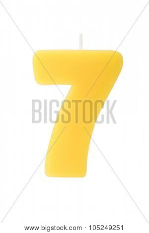 Yelllow birthday candle in the form of the number seven on white background