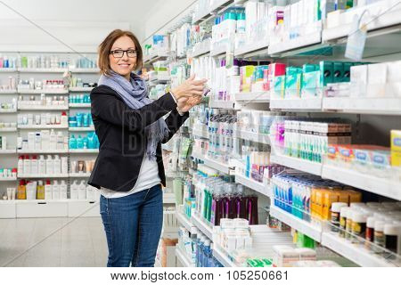 Portrait of smiling mid adult female customer choosing product at pharmacy