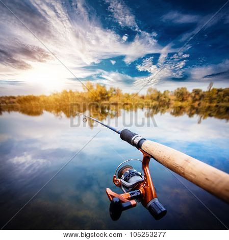 Fishing rod near beautiful pond with cloudly sky