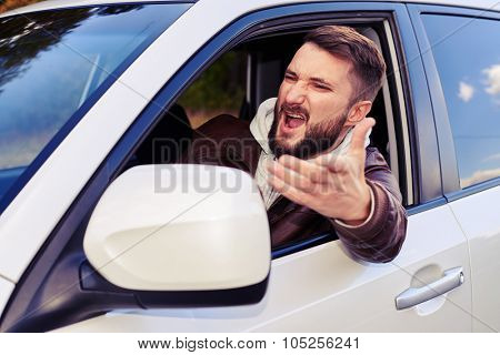discontented young man shouting from the window of his car