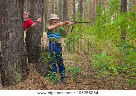 Two hunters shoot in coniferous forest