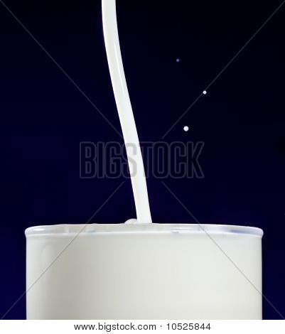 Glass of milk with splashing drops on deep blue poster