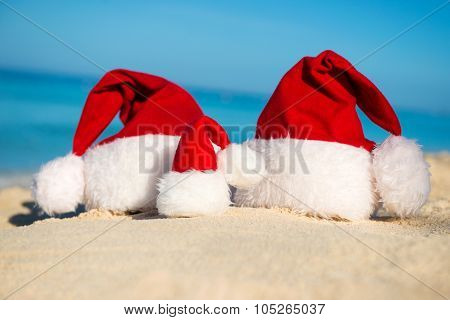 Santa Hats On Sandy Beach  - Concept Of New Year Family Holiday With The Children On The Sea.