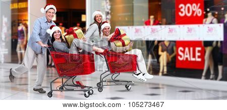 Happy couple with gift in shopping mall. Christmas sale.