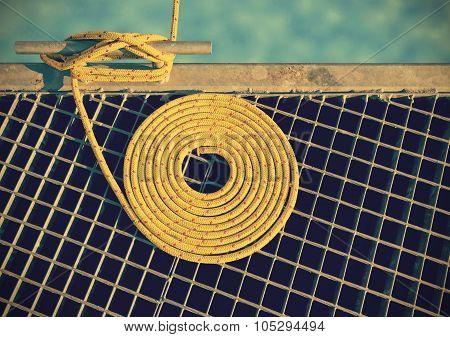 Retro Toned Marine Background Made Of Mooring Rope On Pier.