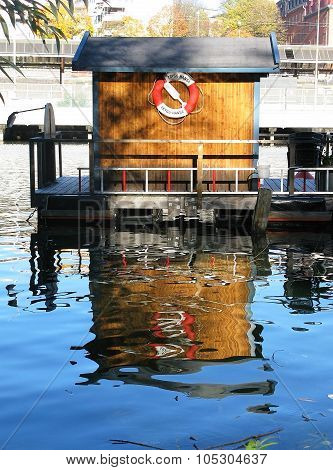 Boat house with life ring reflected in water