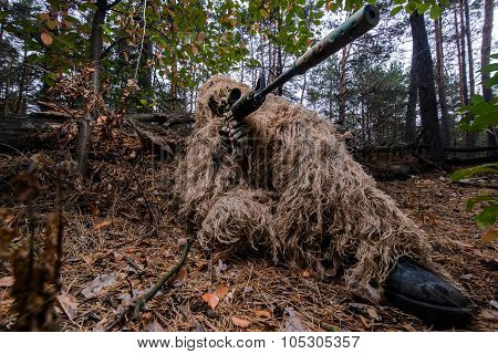 Camouflaged Sniper In Forest Aiming Through Scope