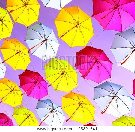 Colorful umbrellas background. Colourful umbrellas urban street decoration. Hanging Multicoloured umbrellas over blue sky. Bright Colors backdrop. Holiday background
