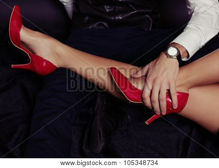 woman's leg in red shoes of chest of handsome man wearing business suit