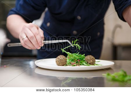 Chef in hotel or restaurant kitchen cooking, only hands