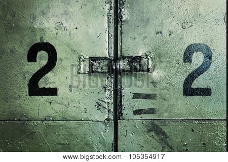 Two number twos on a dirty industrial wall.