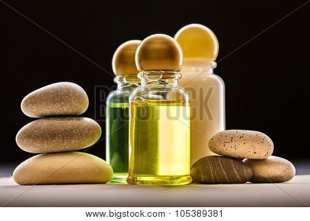 Shampoo bottles with stones on black background poster