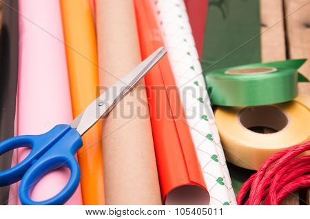 Gift wrapping concept with various paper colors, scissors, tape and other decoratives lying on woode