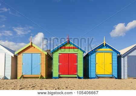 Bathing boxes in a beach against blue sky with copyspace poster