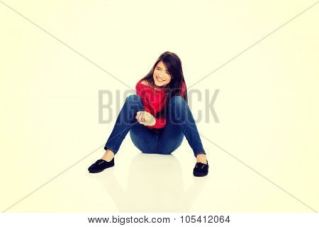 Relaxing laughing student woman sitting on the floor.