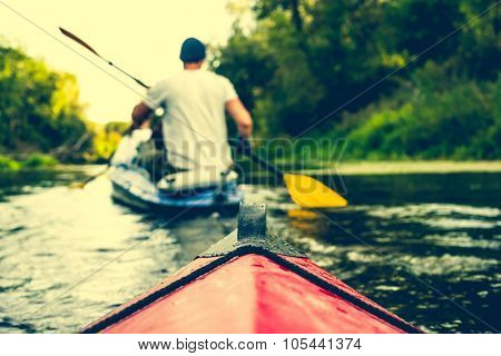 nose of canoe floating behind rower on a river poster
