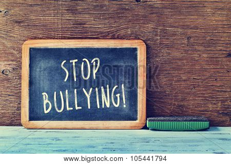 the text stop bullying written with chalk in a chalkboard and an eraser on a blue rustic wooden desk in a classroom