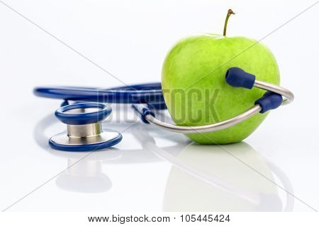 an apple and a stethoscope with a doctor. symbolic photo for healthy and vitamin-rich diet.
