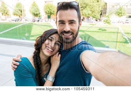 Closeup shot of young couple take selfie outdoor. Young man taking a photo with his girlfriend. Happpy smiling couple taking a selfie in a summer day.