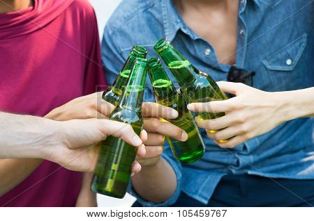 Closeup shot of happy friends toasting with bottles of beer. Girls and guys drinking beer outdoor in a summer day. Close up of female and male hand holding a bottles of beer.