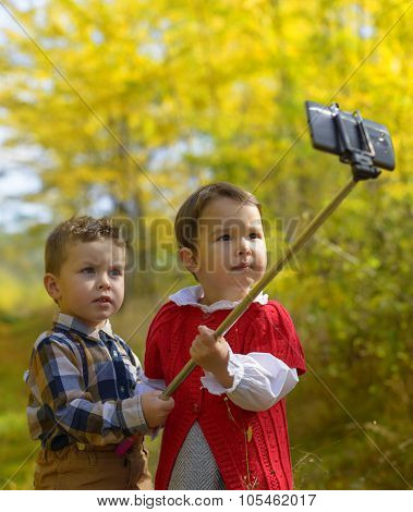 Two Little Kids Taking Selfie In Park