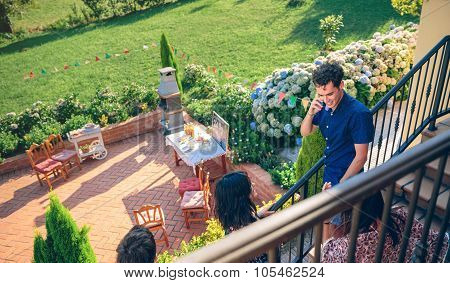 Young man calling by phone over barbecue background