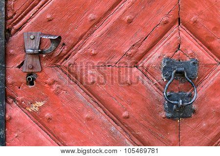 Closeup background of red wooden door with rustic keyhole, doorknob, and door knocker