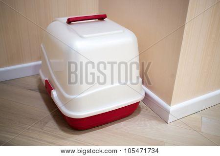 White and red litterbox standing in corner of corridor.