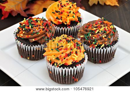 Autumn Chocolate Cupcakes With Orange And Chocolate Frosting And Sprinkles.  Selective Focus On Fron