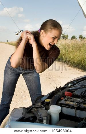 Furious young woman threaten with lug wrench at the car engine.