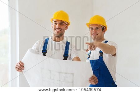 building, teamwork and people concept - group of smiling builders in hardhats with blueprint indoors