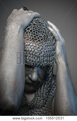 Conflict, man in chain mail and leather painted silver, medieval warrior