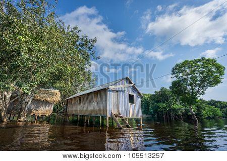 Woode houses built on high stilts over water, Amazon rainforest