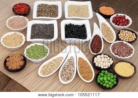 Health and body building super food with whey protein, wheat grass, acai berry and maca powder, nuts, seeds, pulses, grains, cereals, fruit, vegetables and peanut butter.