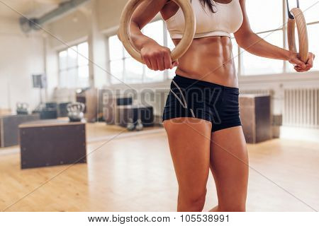 Female Athlete Exercising With Rings At Crossfit Gym