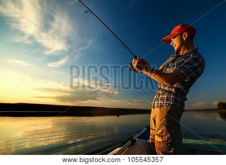 Young man fishing on the pond from the boat