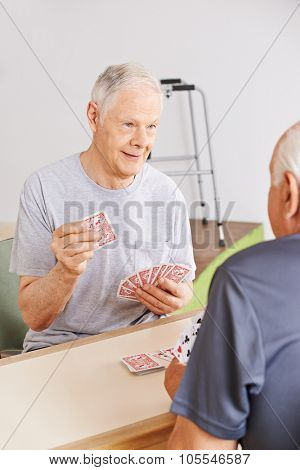 Two senior people playing cards in a nursing home