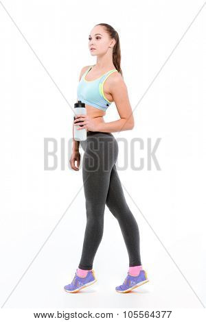 Young beautiful sportswoman in blue top and grey leggins on tiptoe with bottle of water