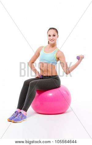 Young beautiful happy smiling sportswoman in blue top and grey leggins with dumbbells exercising on fitball