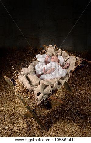 Baby Jesus on a manger inside old dark stable