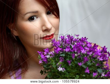 Redhead young woman is holding violet campanula flowers. poster
