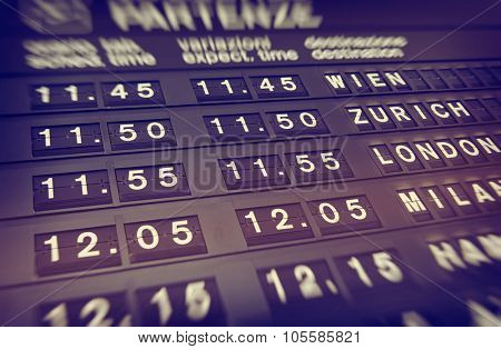 Illuminated departures board at an airport giving the flight details for upcoming flights and departures in a transport and travel concept
