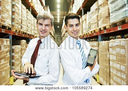 two managers workers in warehouse with tablet computer