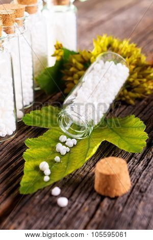 Homeopathic lactose sugar globules on leaf with glass bottle
