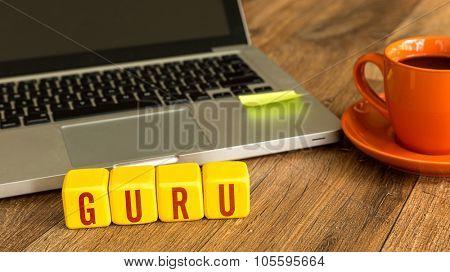 Guru written on a wooden cube in front of a laptop