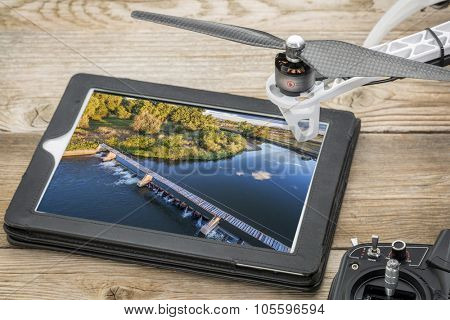 drone aerial photography concept - reviewing aerial picture of a river diversion dam on a digital tablet with a drone rotor and radio control transmitter, poster