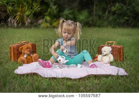 Sweet blonde-haired little girl pouring tea at a teddy bear picnic. poster